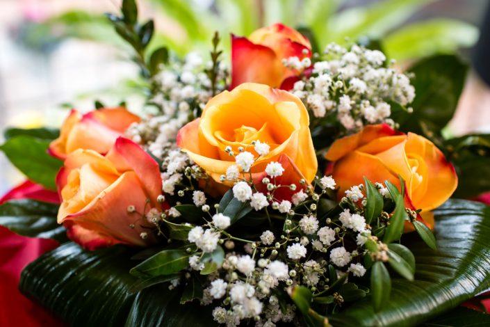 Blumenstrauß mit orangen Rosen und weißen Blüten